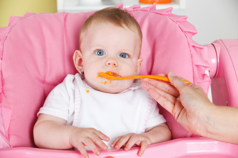 Baby eating carrot stock photo