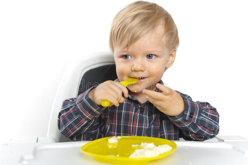 Baby eating on a child chair on white. Background stock photos