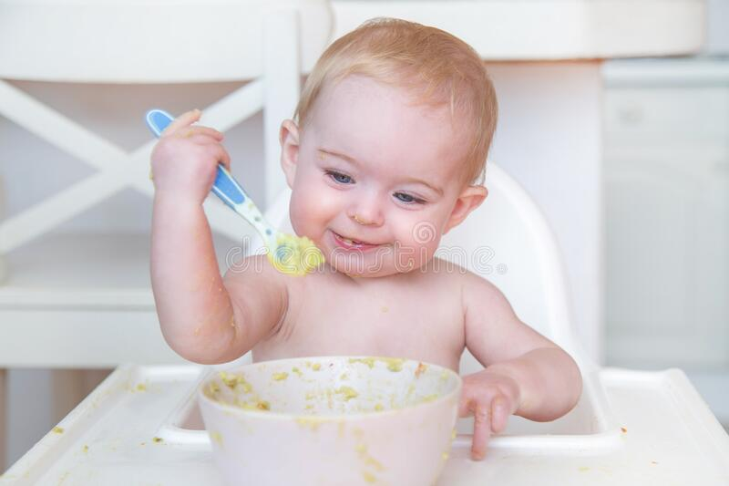 baby eating first solid food royalty free stock photos