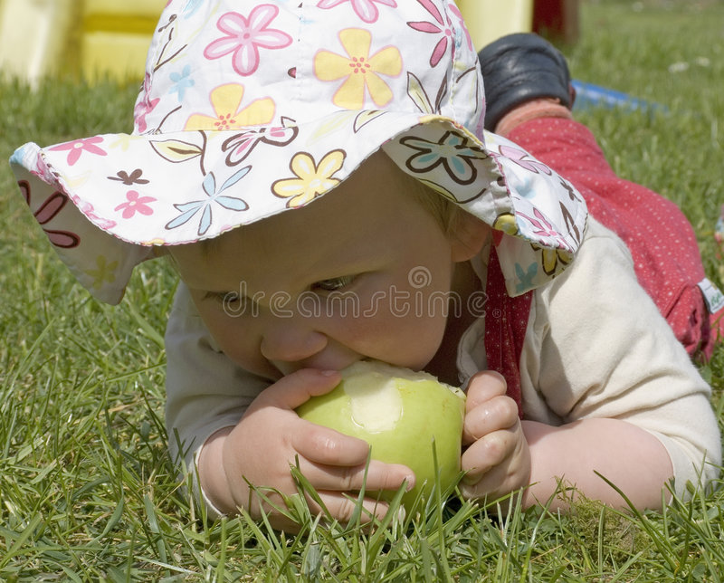 Baby eating a green apple. A baby child with sun hat on the meadow eatin a green apple stock photos