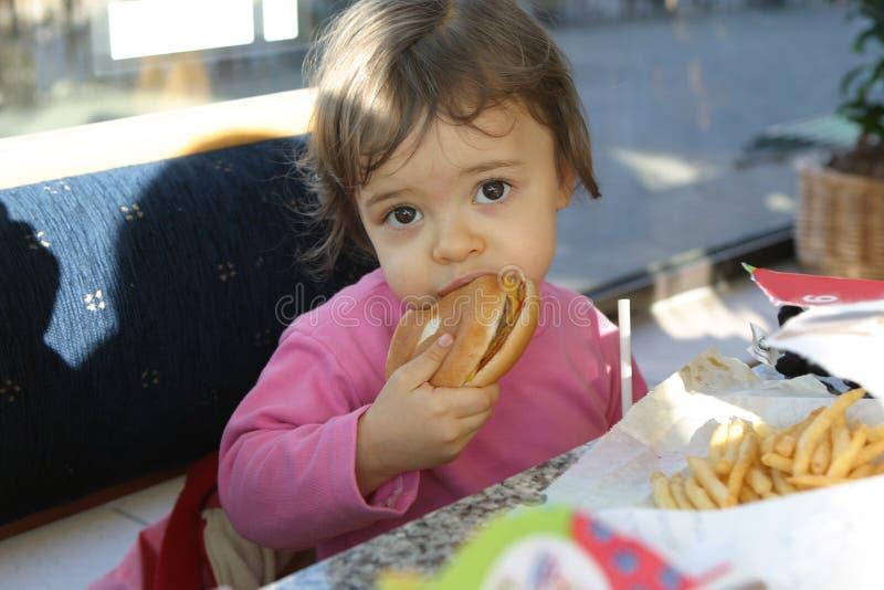 Baby eating hamburger. Young baby is eating hamburger stock images