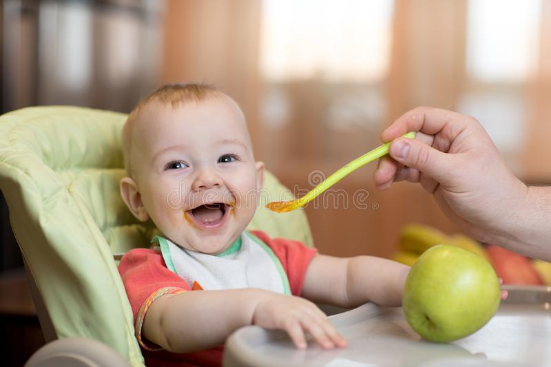 Baby eating healthy food with father help at home royalty free stock photography