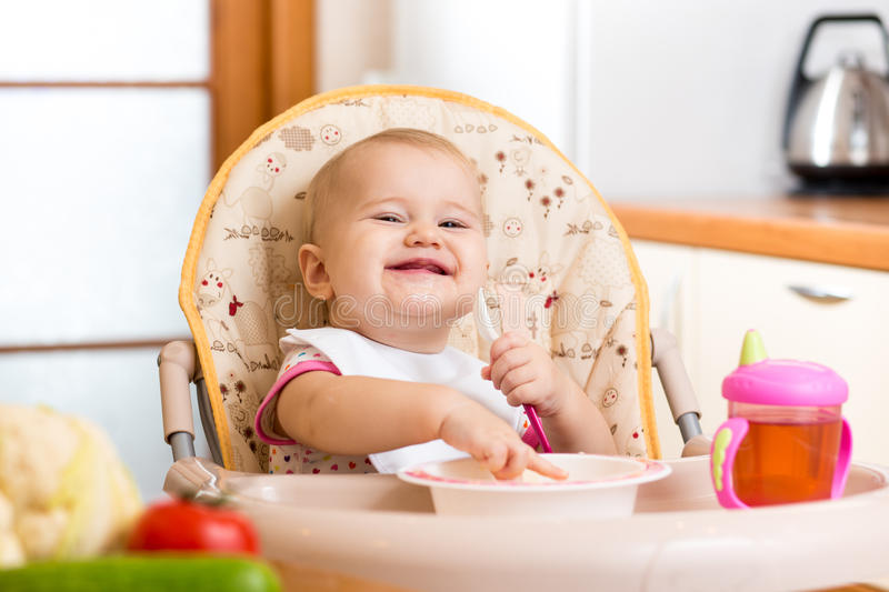 Baby eating healthy food on kitchen royalty free stock photo