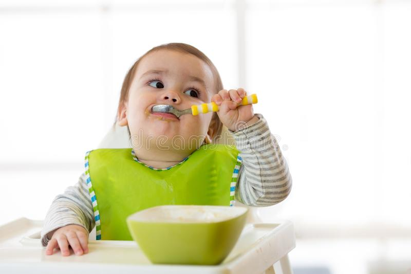 Baby eating healthy food with the left hand at home stock image