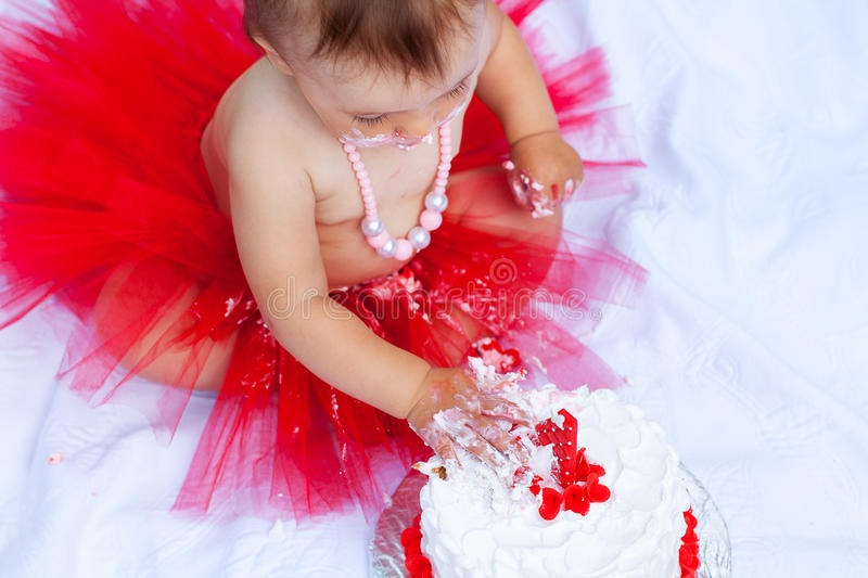 Baby eating her first birthday cake. Baby in red tutu eating her first birthday cake; top view stock photos