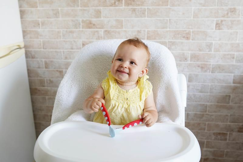 Baby eating at kitchen empty space table.Child`s nutrition stock photo