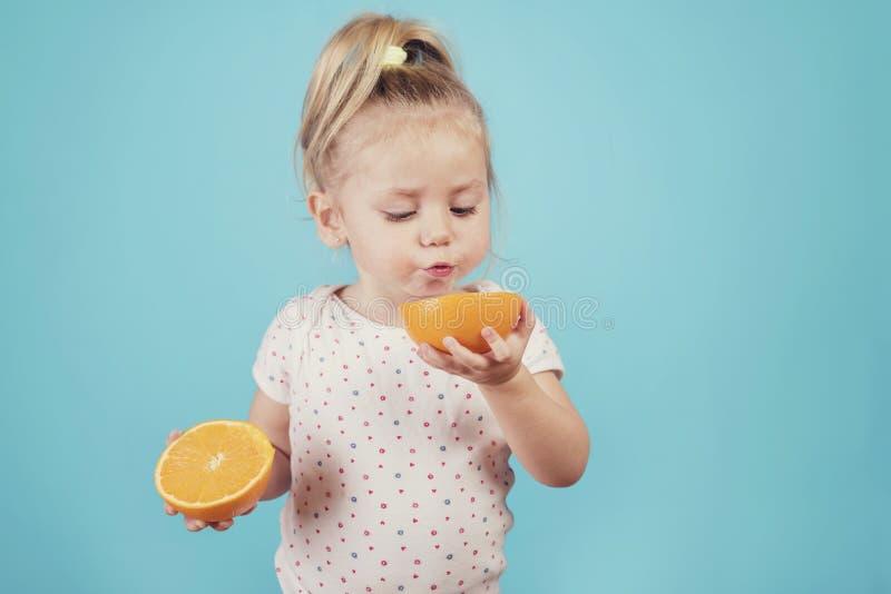 Baby eating an orange stock photos