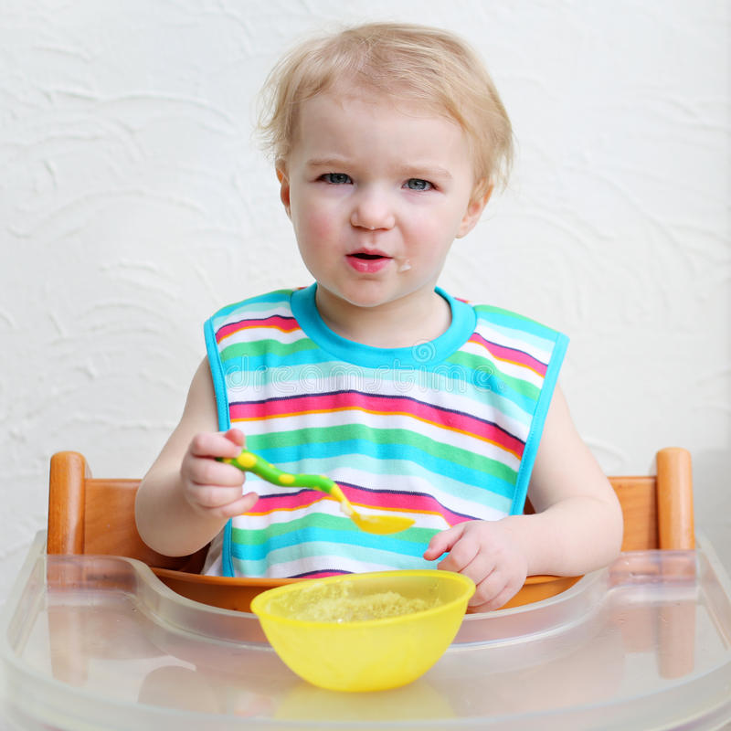 Baby eating porridge from bowl stock photo