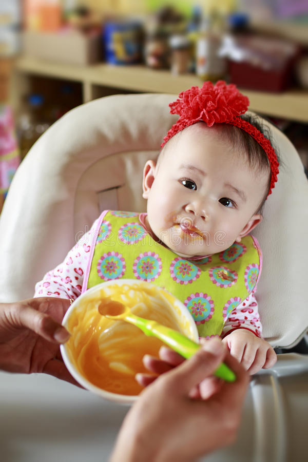Baby Eating Solid Food. Portrait of 9 month old baby girl eating solid food stock photo