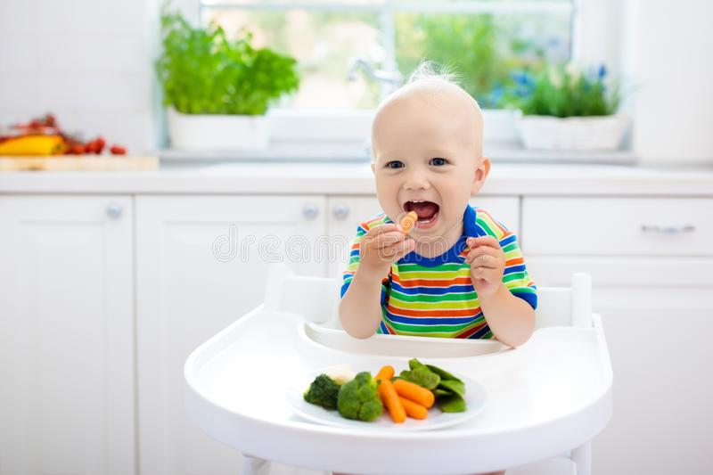 Baby eating vegetables in kitchen. Healthy food. Cute baby eating vegetables in white kitchen. Infant weaning. Little boy trying solid food, organic broccoli royalty free stock photos