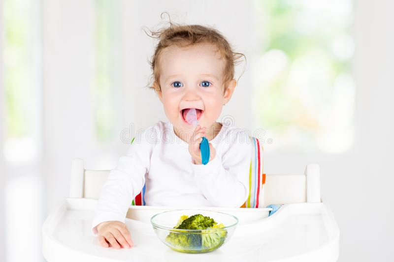 Baby eating vegetables. Solid food for infant royalty free stock image