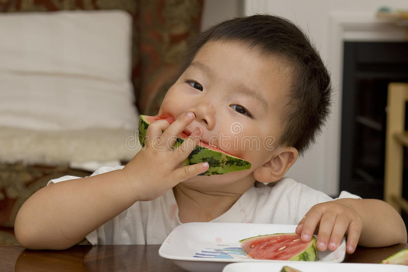 Baby eating watermelon royalty free stock photos