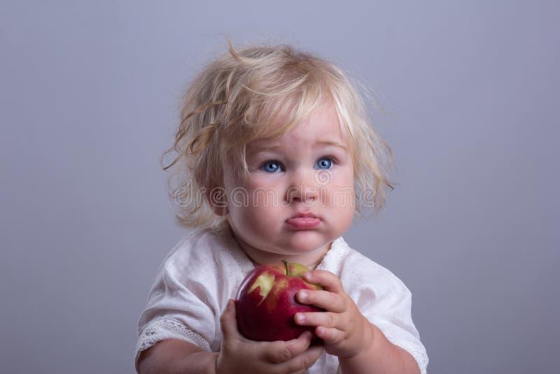 Baby ein roter Apfel lizenzfreie stockbilder