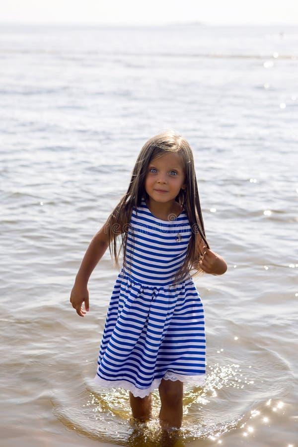 Baby in einem gestreiften Kleid und in den Läufen lizenzfreie stockfotografie