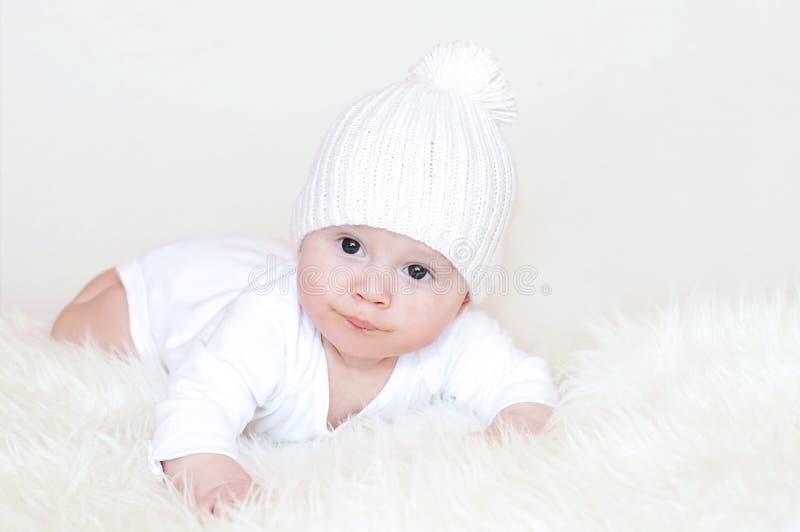 Baby in einer weißen Strickmütze stockbild