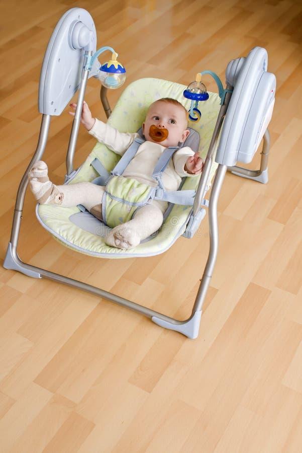 Baby in elektronische schommeling stock afbeeldingen