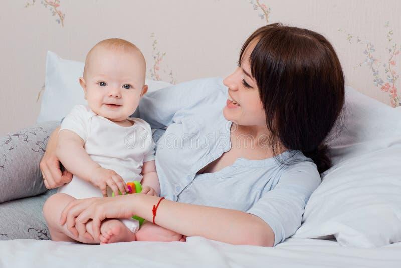 Baby en mamma die in hun pyjama's in een goede stemming op het bed spelen, royalty-vrije stock afbeeldingen