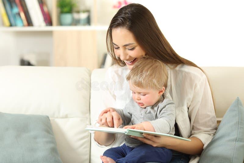 Baby en moeder die een boek samen lezen stock foto's