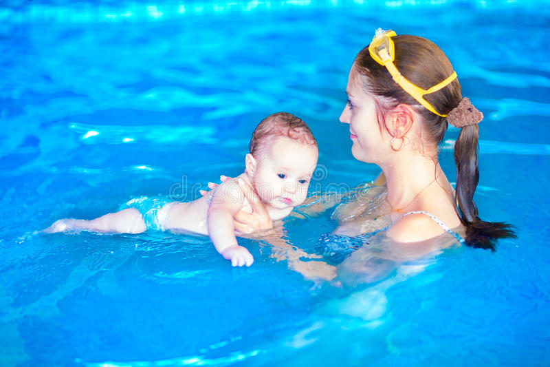 Baby en moeder in zwembad stock foto's