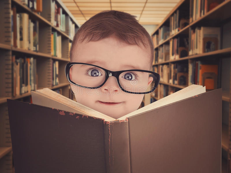 Baby with Eye Glasses Reading Library Book. A cute little baby is wearing eye glasses and reading a library book for an education or learning concept stock photo