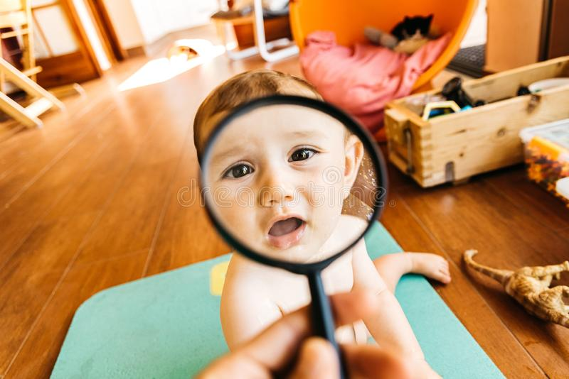 Baby face while playing with a magnifying glass, which makes a funny and tender face.  royalty free stock photo