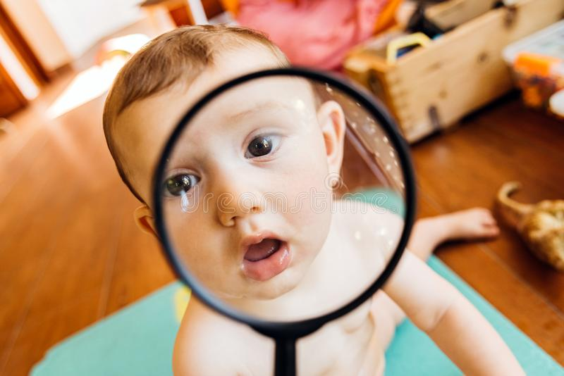 Baby face while playing with a magnifying glass, which makes a funny and tender face.  royalty free stock photos