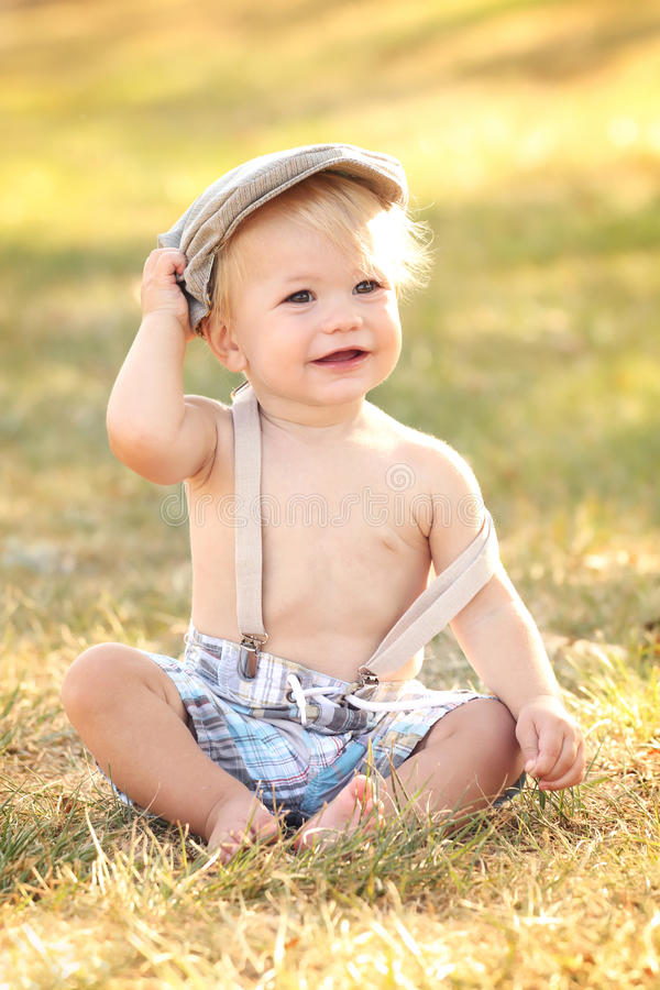 Baby, Fall. Baby, toddler boy wearing suspenders and a country / newsboy hat, outdoors, featuring seasonal, fall colors, suitable for Thanksgiving or Halloween royalty free stock images
