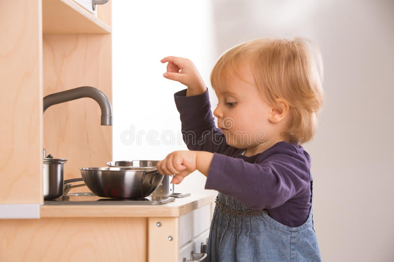 Baby family girl daughter play cooking in toy kitchen royalty free stock image