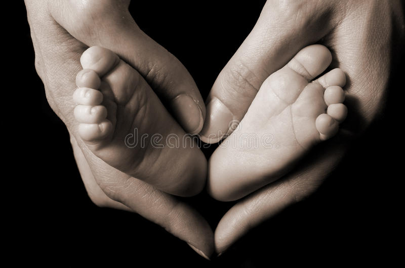 Mother holds newborn baby feet in a heart royalty free stock photography