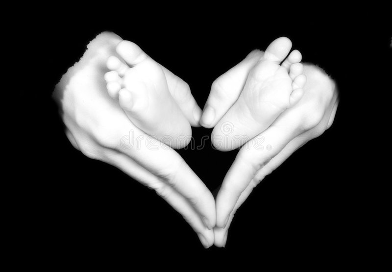 Baby Feet. Held by mother's hands making heart shape royalty free stock image