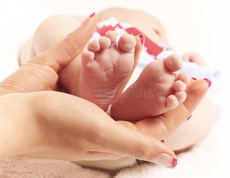 Baby feet in hands stock photos