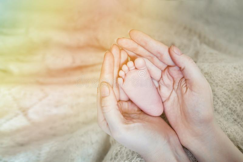Baby feet in mother hands. Mom and her Child. Happy Family concept. Beautiful conceptual image of Maternity stock image