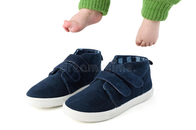 Baby feet with too big blue child shoes isolated on white royalty free stock photography