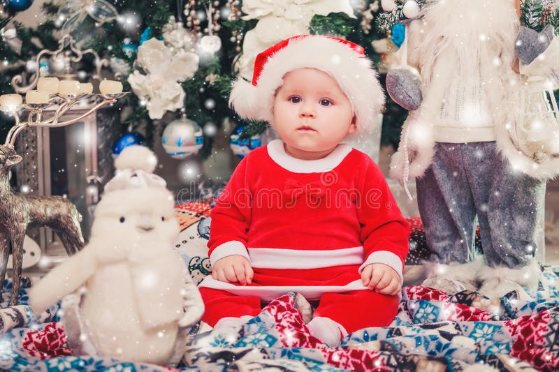 Baby first Christmas. New Year holidays. Baby with santa hat with gift. stock images