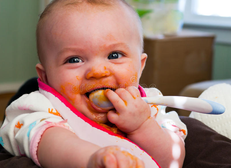 Baby Food Introduction. Four month old infant girl enjoying baby food sweet potatoes stock image