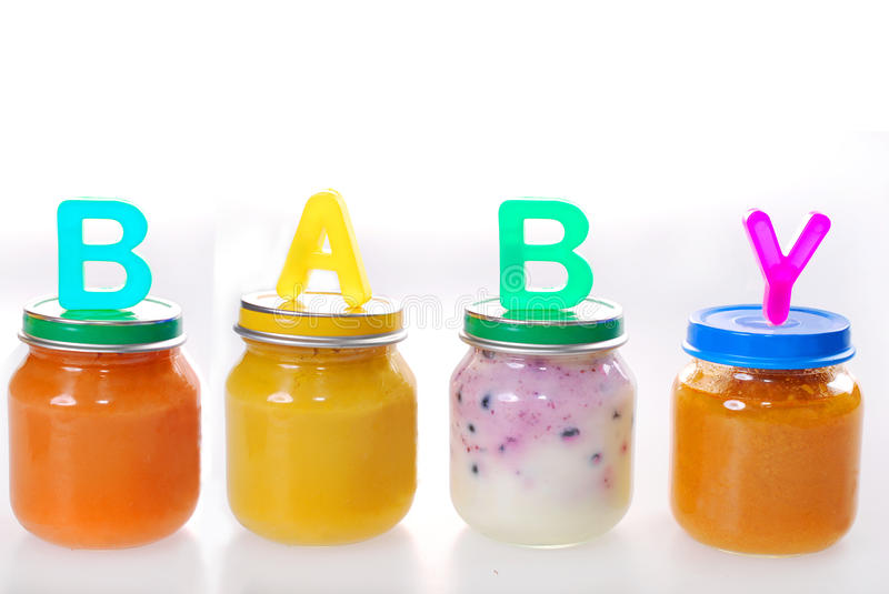 Baby food in jars. Assortment of baby food in jars with letters making word baby on the top isolated on white royalty free stock images