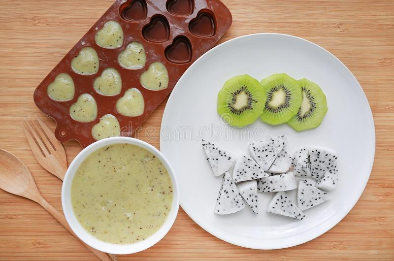 Baby food mashed in container on wooden board for freezing with plate of sliced dragon fruit and kiwi royalty free stock photo