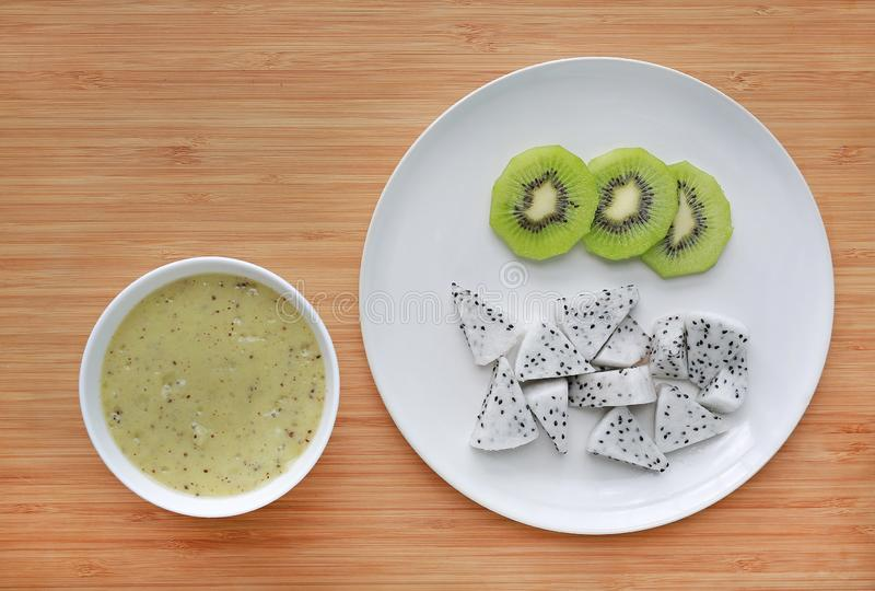 Baby food mashed in white bowl on wooden board with plate of sliced dragon fruit and kiwi royalty free stock images