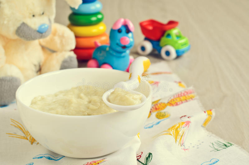 Baby food. On the plate on the background of children's toys stock image