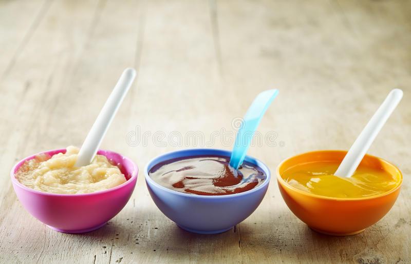 Baby food. Various kinds of baby food in plastic bowls stock photo
