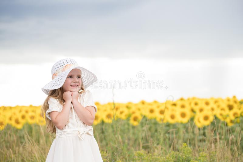 Baby freuen sich, um zu lächeln schönes Mädchen in einem weißen Kleid und in einem weißen Hut stockbilder