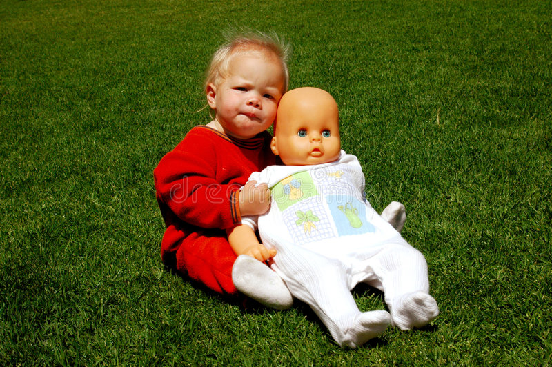 Baby friendship. A full body of a beautiful blond caucasian white baby girl with cute expression in her pretty face sitting on the lawn, holding her big doll in royalty free stock images