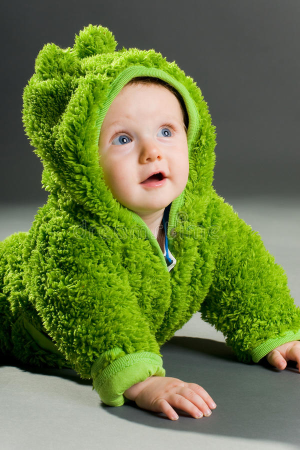 Baby in a frog outfit stock image