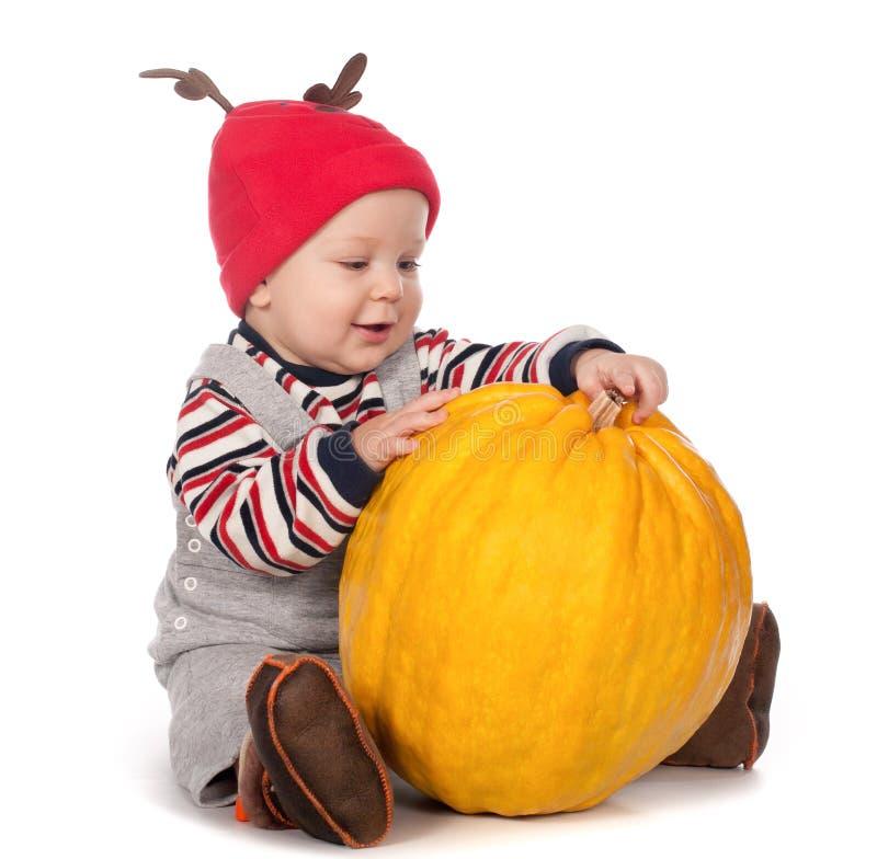 Baby In Funny Deer Hat With Orange Pumpkin Stock Image