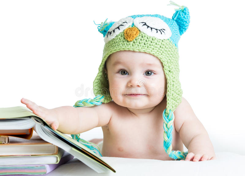Baby in funny knitted hat owl with books royalty free stock photo