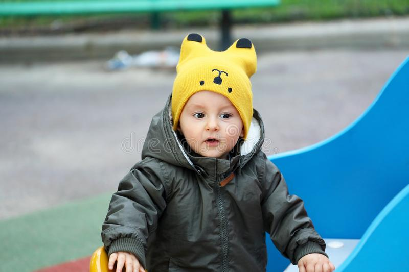Baby With A Funny Yellow Hat And A Winter Jacket stock photos