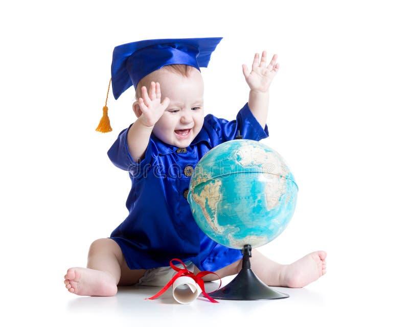 Baby in geïsoleerde academicuskleren met bol stock foto