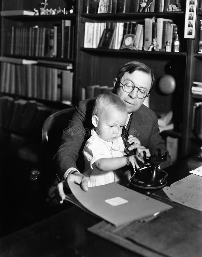 Baby-Gebrauchstelefon des Vaters helfendes (alle dargestellten Personen sind nicht längeres lebendes und kein Zustand existiert L stockfoto