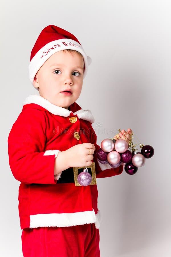 Baby gekleidet als Santa Claus, die Weihnachtsflitter hält. stockbild