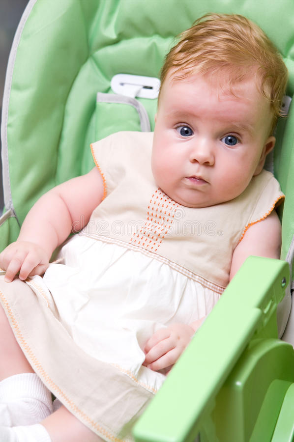 Baby girl. Cute baby girl sitting in feeding chair stock photo